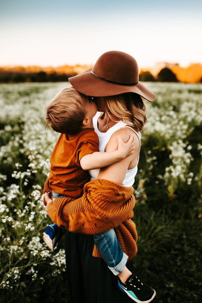 Family Photography, mom holds toddler son in her arms, he kisses her on the cheek, they are in a flower-filled field