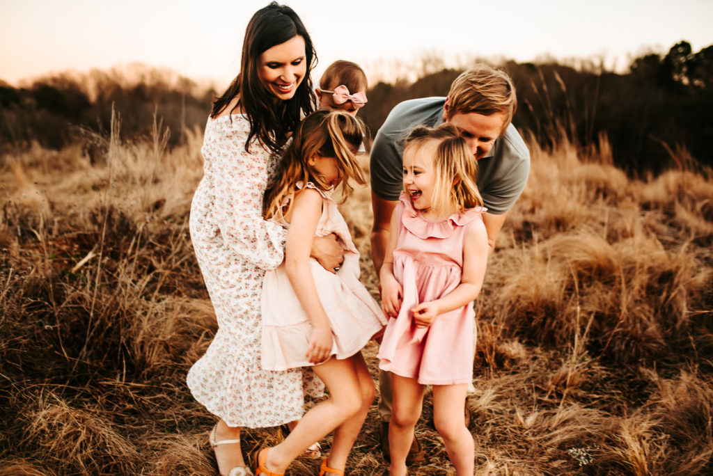 Family photography, mom , dad and kids all laugh and hold each other tightly outside in a field