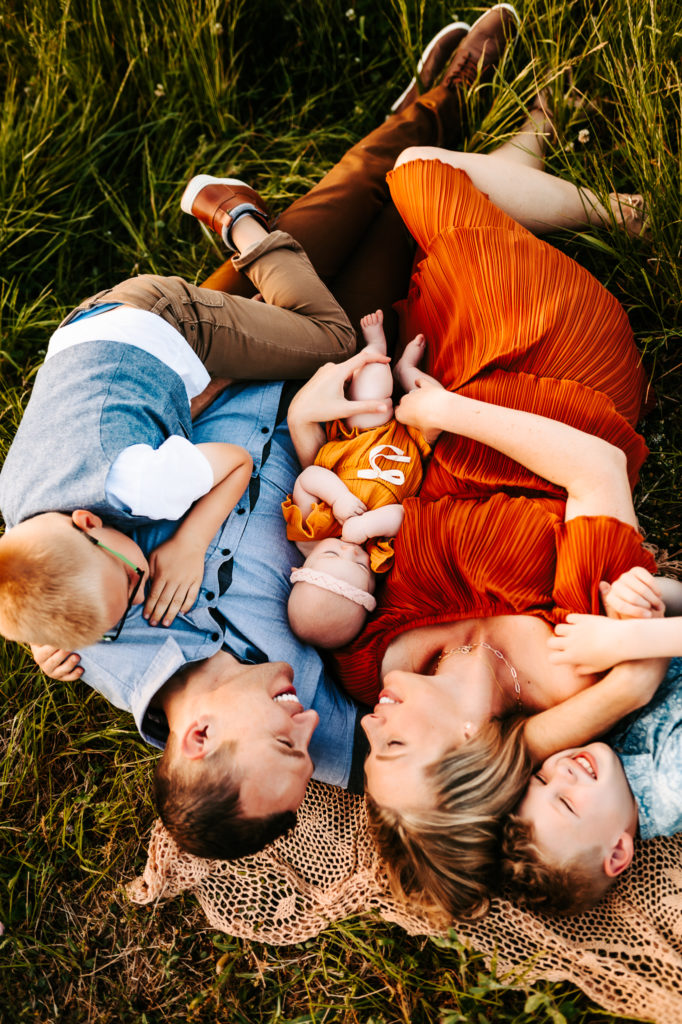 Family Photography, a family lays on a blanket in the grass all smiling