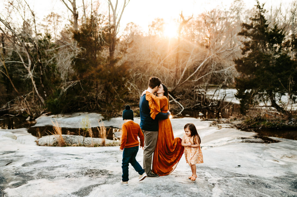 Family Photography, husband and wife hold each other on a snow day, their children dance around them happily