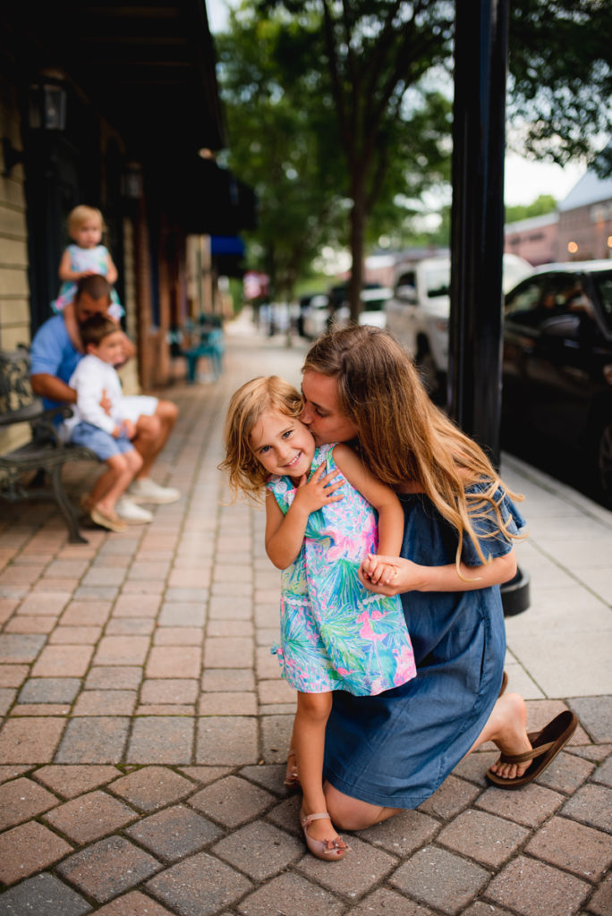 Family Photographer, mother kneeling down on sidewalk to give daughter a kiss