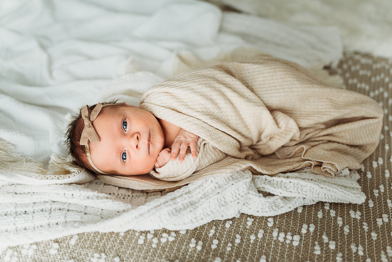 Newborn photography, a baby lays snuggled in a white blanket with a bow in her hair